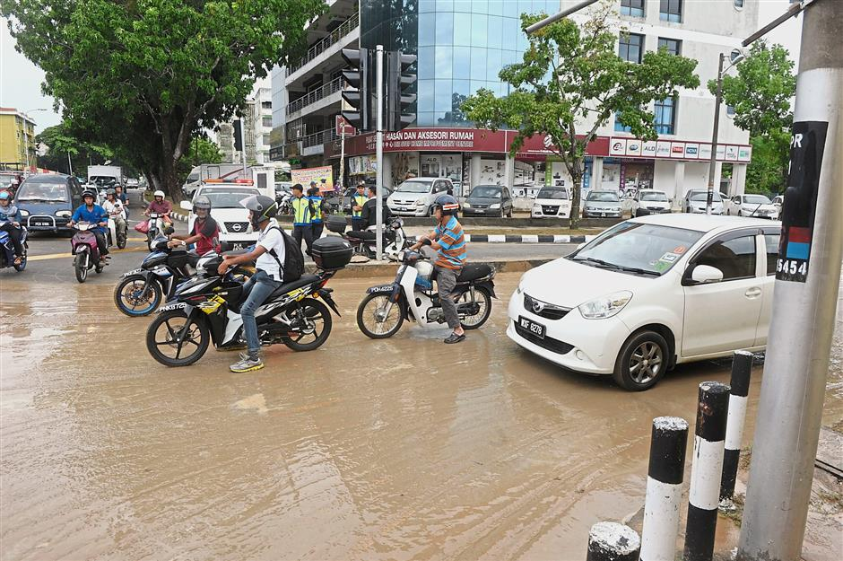 (Left) Vehicles stopping at a traffic light junction in Jalan P. Ramlee where muddy waters are flowing.(Right) Vehicles stuck in floodwaters along Patani Road.