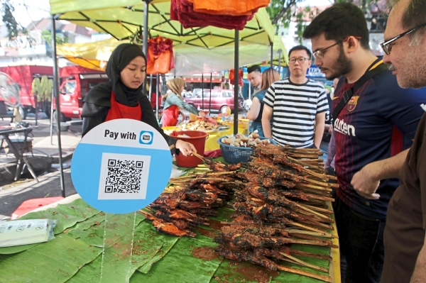 Why bother carrying cash when you can use eWallets at Ramadan bazaars in town. — ART CHEN/The Star