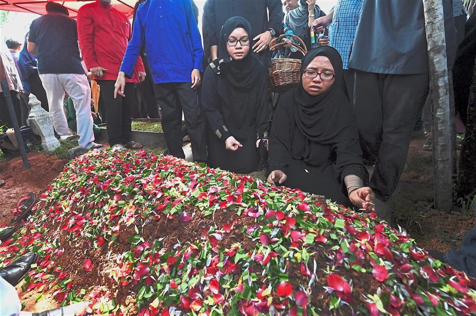 Loss and grief: Amanda (right) placing flowers on her fatheru2019s grave at the Bukit Kiara cemetery in Kuala Lumpur. u2014 Bernama