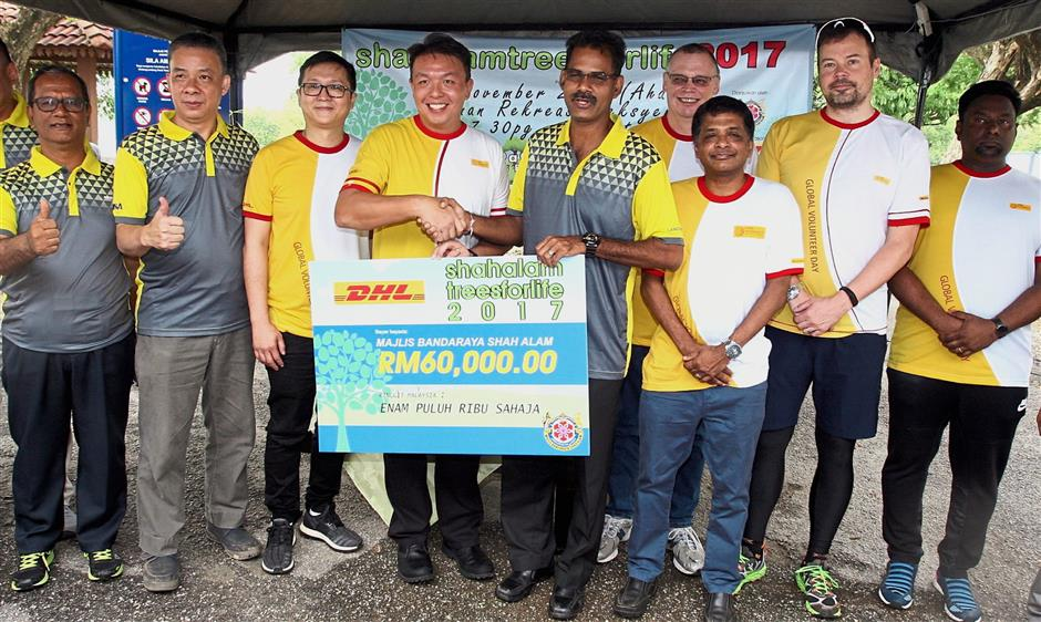 Ong (fourth from left) handing over a mock cheque to Papparaidu as part of DHL's contribution to the Shah Alam Trees For Life initiative. With them are DHL Malaysia directors and MBSA councillors.