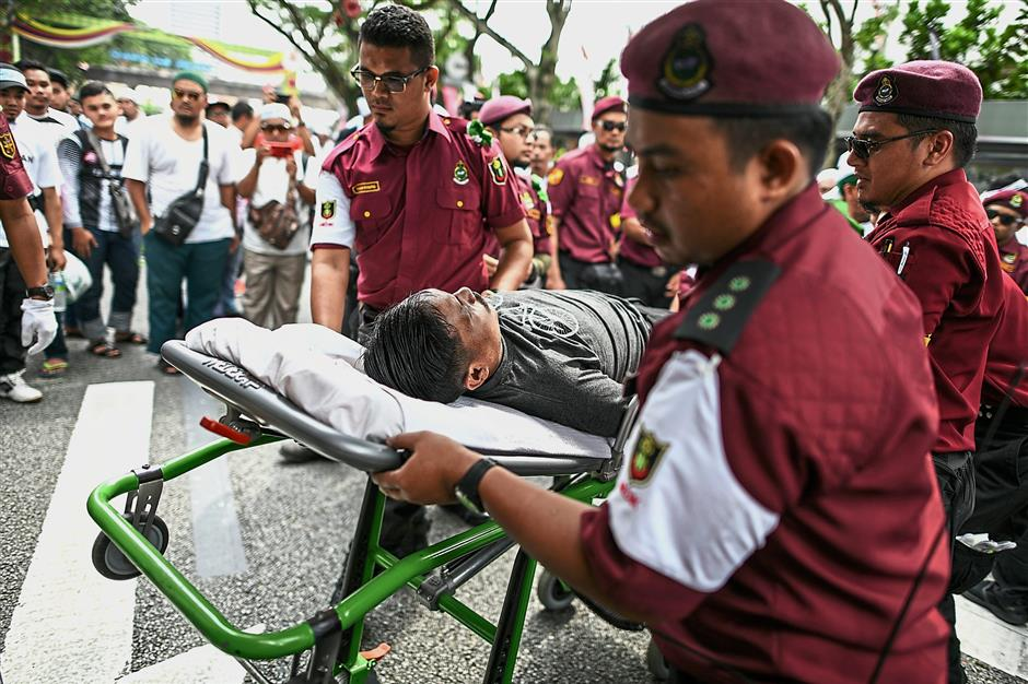 Quick to respond: Medics evacuating a protester who fainted during the rally. — AFP