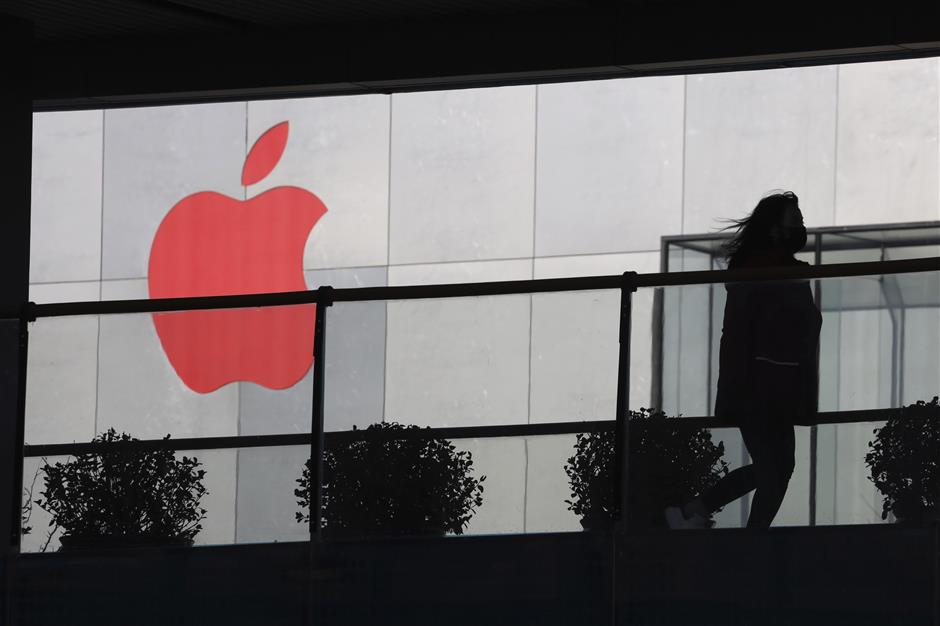 In this Dec. 6, 2018, photo, a woman runs past a Apple logo colored red in Beijing, China. Apple Inc.u2019s $1,000 iPhone is a tough sell to Chinese consumers who are jittery over an economic slump and a trade war with Washington. The tech giant became the latest global company to collide with Chinese consumer anxiety when CEO Tim Cook said iPhone demand is waning, due mostly to China. Weak consumer demand in the worldu2019s second-largest economy is a blow to industries from autos to designer clothing that are counting on China to drive revenue growth. (AP Photo/Ng Han Guan)