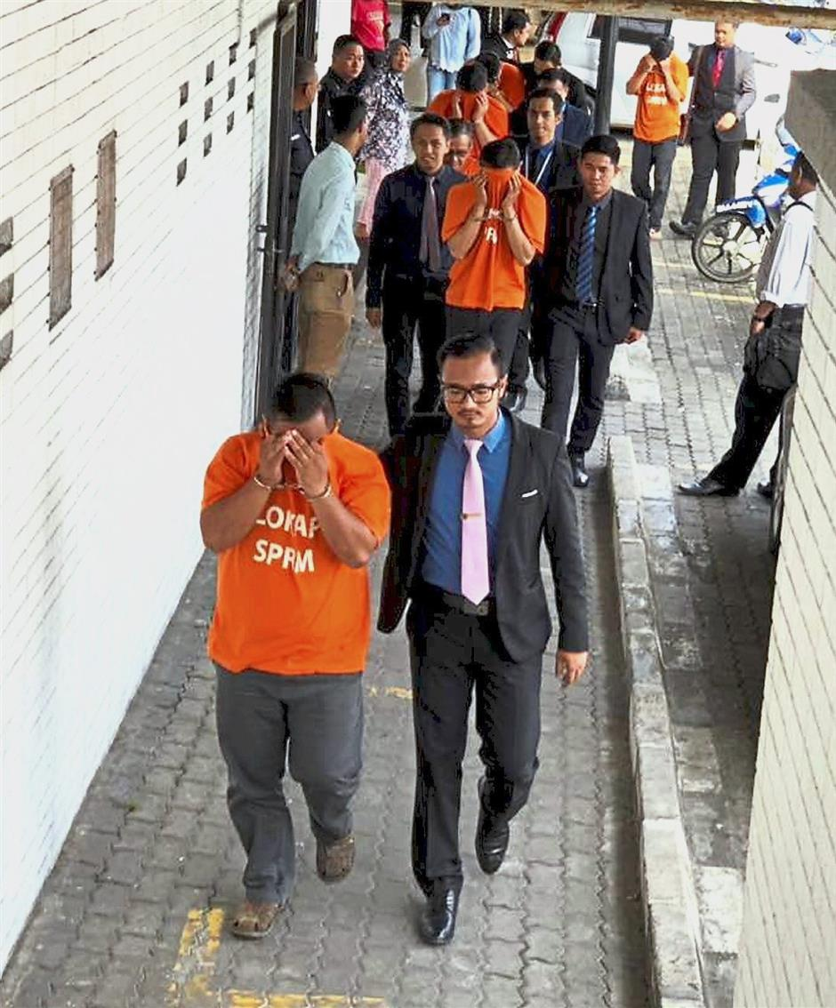 In a spot: MACC officers escorting the suspects held in the Sabah Railway Department probe at the Kota Kinabalu court house.