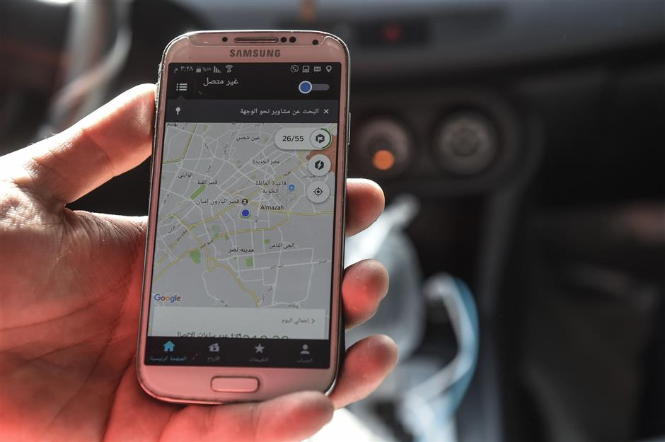 Ramez Wagih, an accountant in the morning and Uber driver in the afternoon, displays a map on his telephone in the Egyptian capital Cairo on April 19, 2018. New legislation regulating ride hailing services in Egypt may have been welcomed by Uber and competitor Careem, but some behind the wheel fear they could be driven out of business. / AFP PHOTO / MOHAMED EL-SHAHED