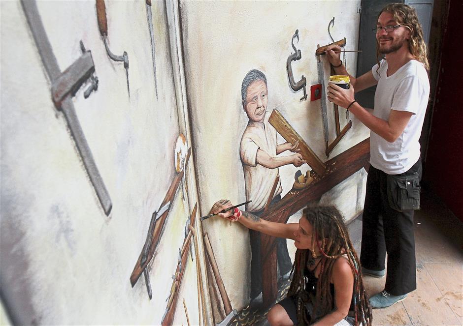 Poschmann (left) and Turello putting the final touches to their wall art.