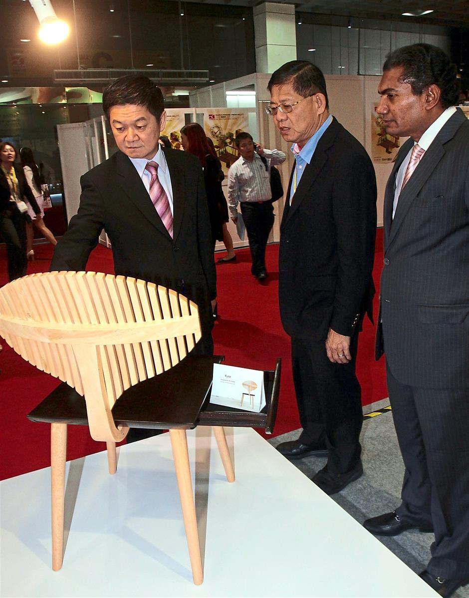 Unique design: (From left) Lee, MIFF chairman Datuk Dr Tan Chin Huat and UBM Asia managing director (Asean Business) M. Gandhi looking at a design called 'Kyte' by one of the 10 finalists, Lim Bo Qiang.