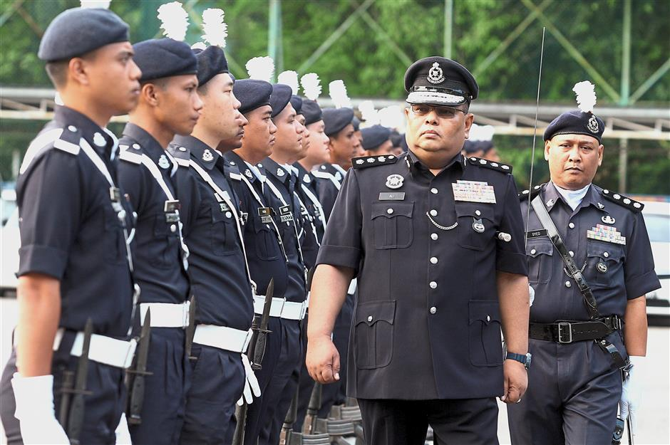 Gombak OCPD ACP Ali Ahmad checking the guard of honour during the Gombak Police headquarters monthly assembly.