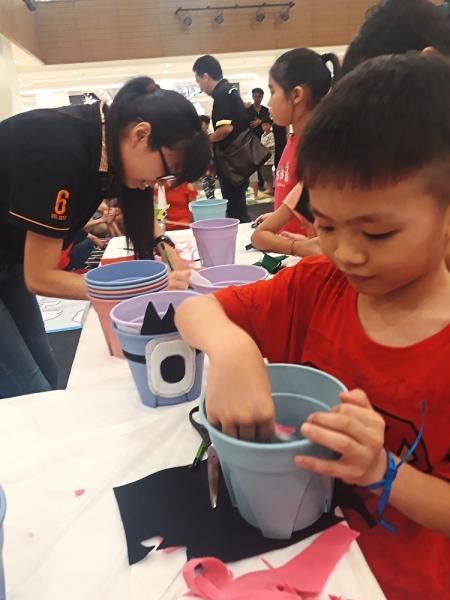 A participant decorating a flower pot.