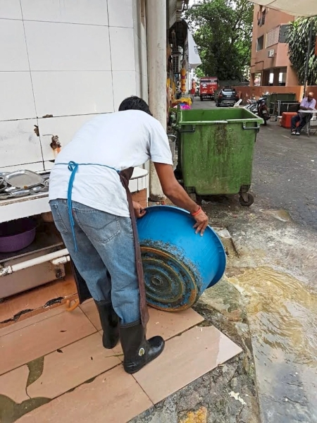 A restaurant worker caught in the act of dumping dirty and oily water directly into drains of Brickfields. — Filepic