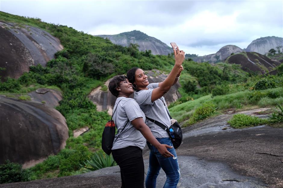 Nigerians take selfies at Idanre hills on August 25, 2018. (Photo by Florian PLAUCHEUR / AFP)