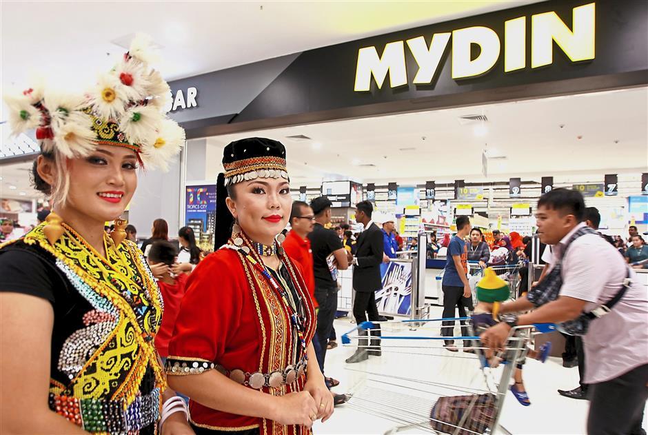 Orang Ulu Shirley Jamaq (left) and Bidayuh Siti Mazura Abdullah in front of Mydin hypermarket at its opening ceremony.