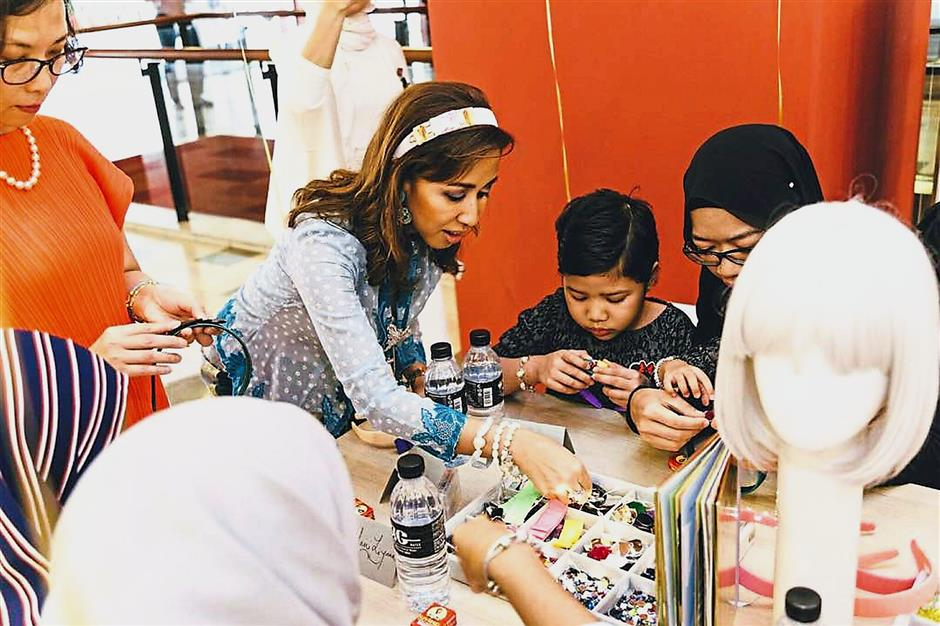 Tengku Zatashah assisting some of the children as they design their very own complimentary custom headbands.