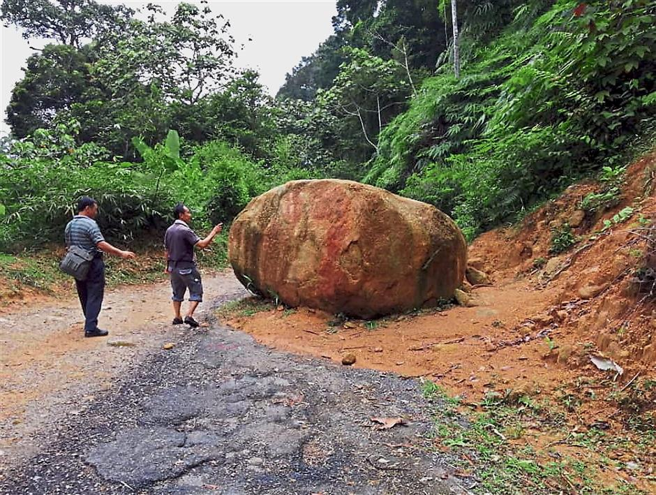 Hikers looking at the boulder still lying on the road. — pic courtesy of hikers