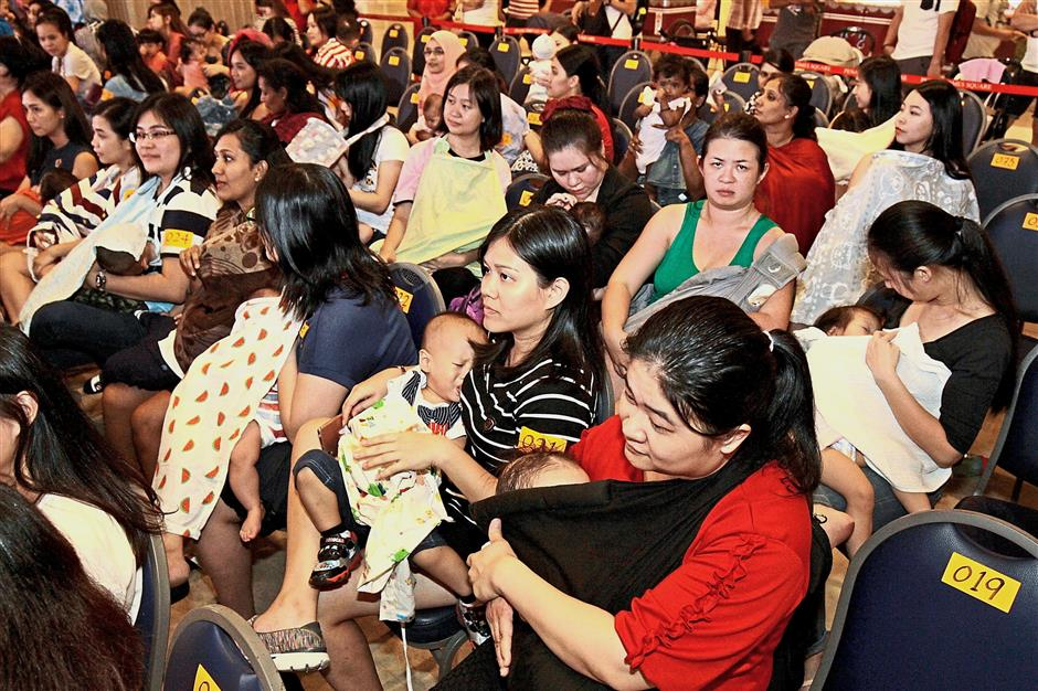 Mothers breastfeeding their babies during the Malaysian Big Latch (Penang) at M Mall in Penang Times Square. (Below, middle) Chong Eng and some of the committee members having a light moment during the event.u2014 Photos: CHAN BOON KAI/The Star