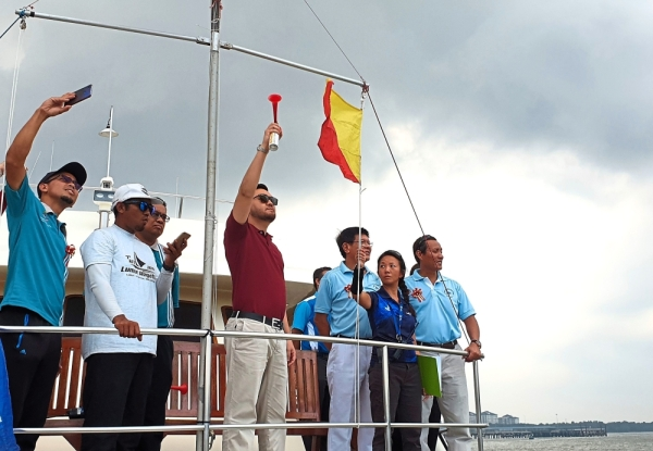 Tengku Amir (third from left) using an air horn to indicate the start of race for the mini regatta held during the launch of the sailing programme.