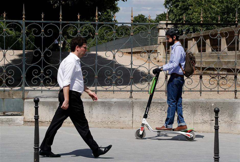 (FILES) In this file photo taken on July 9, 2018, a pedestrian (L) walks as a man uses an electric scooter of US company Lime in Paris. - France will ban electric scooters from pavements in September, the transport minister said May 4, 2019, in a backlash against a surge of the commuter gizmos invading pedestrian areas. An estimated 15,000 scooters operated by several companies have flooded the French capital since their introduction last year, a number projected to surge to 40,000 by the end of this year. (Photo by FRANCOIS GUILLOT / AFP)