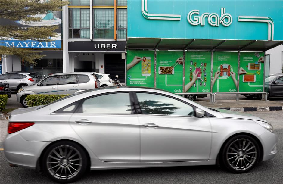 A car passes a Grab passenger stand and an Uber office in Penang, Malaysia April 4, 2018. Picture taken April 4, 2018. REUTERS/Edgar Su
