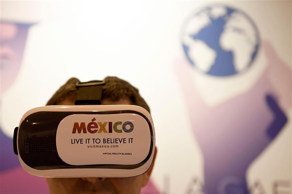A man uses virtual reality glasses at the Mexico stand during the International Tourism Fair (FITUR) in Madrid on January 17, 2018. / AFP PHOTO / GABRIEL BOUYS