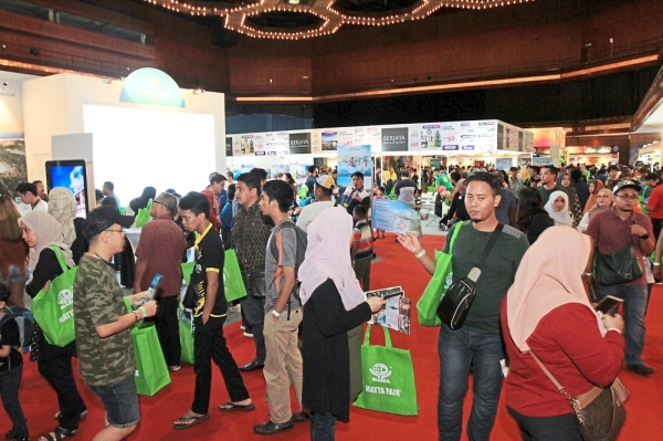 Visitors holding on to their goodie bags while checking out travel deals.