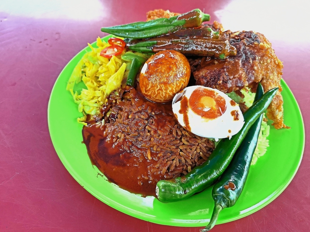 (Left) Nasi kandar special is served with a piece of fried chicken, green chillies, ladies' fingers, a hard-boiled egg, cabbage and salted egg.(Far Left) The queue at Salman Nasi Kandar builds up from 12.30pm.