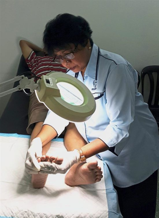 Gnanam checking the condition of a patient's foot.