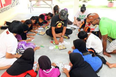 Doing good: Volunteers from Star Publications (M) Bhd guiding village kids during an arts and craft session. Such activities allow employees to step out of their shells and explore their hidden talents.