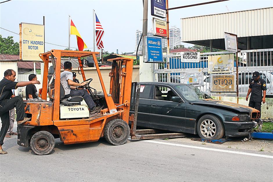 A forklift being used to lift an abandoned car before it is towed away by MBPJ. — Photos: BRIAN MOH /The Star
