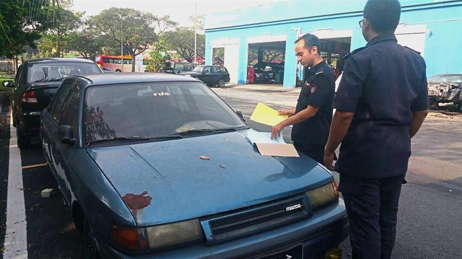 MBSA enforcement officers placing a notice on an abandoned car in Taman Sri Muda, Shah Alam.