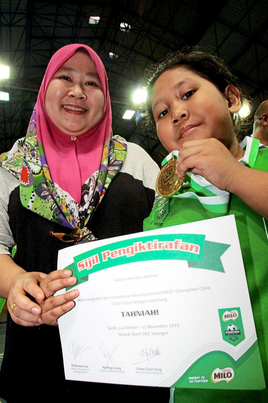 Nurdhiyaa with mother Norizan as she shows off her medal and certificate of participation.