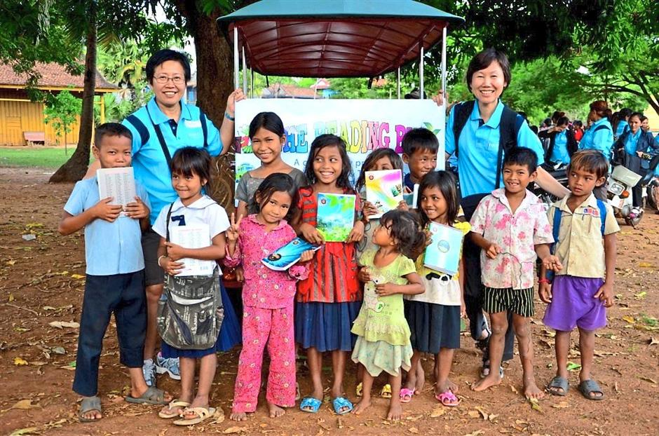 Khmer touch: Volunteers posing with children from the Reading Tuk-tuk in Cambodia.