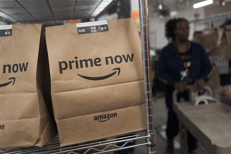 In this Wednesday, Dec. 20, 2017, photo, Prime Now customer orders are ready for delivery at the Amazon warehouse in New York. (AP Photo/Mark Lennihan)