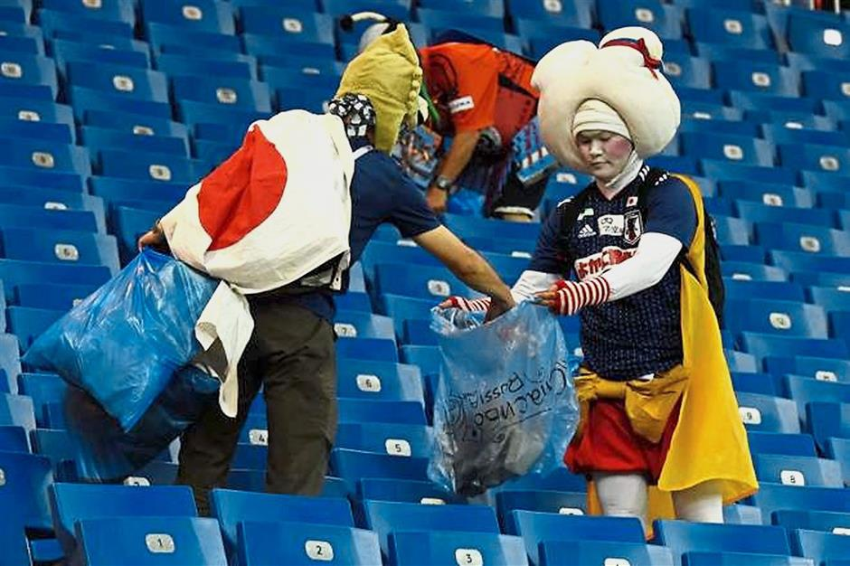 Educated well: Japanese football fans cleaning up after a match at the World Cup tournament in Russia. – AFP/Getty