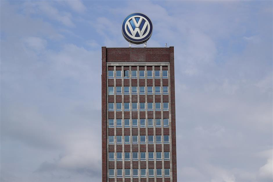 The Volkswagen AG (VW) logo sits above the automaker\'s headquarters in Wolfsburg, Germany, on Friday, April 13, 2018. Volkswagen AGu2019s new top manager pledged to speed up the German carmaking giantu2019s decision-making as it confronts a seismic industry change in technology while moving beyond its diesel-emissions scandal. Photographer: Krisztian Bocsi/Bloomberg
