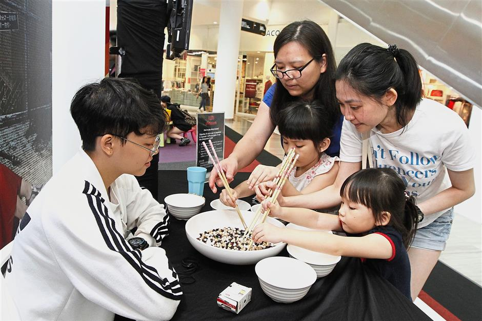 Visitors trying to sort out nuts using chopsticks at the Taiwan pavilion at the event.