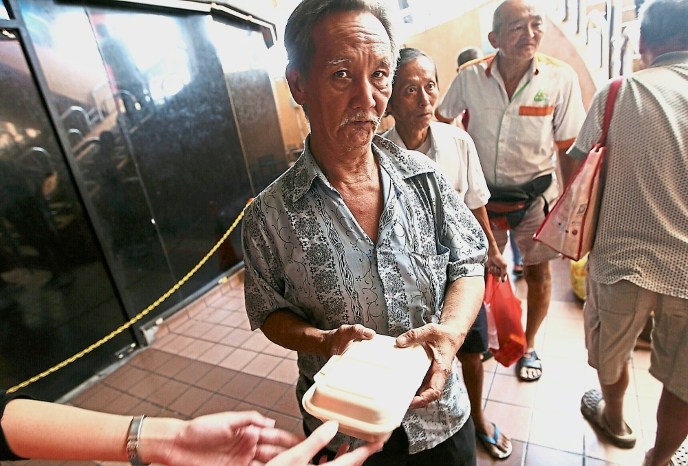 Senior citizens lining up for their meal packets. Some claim that there are up to 200 homeless people in the Pudu area.