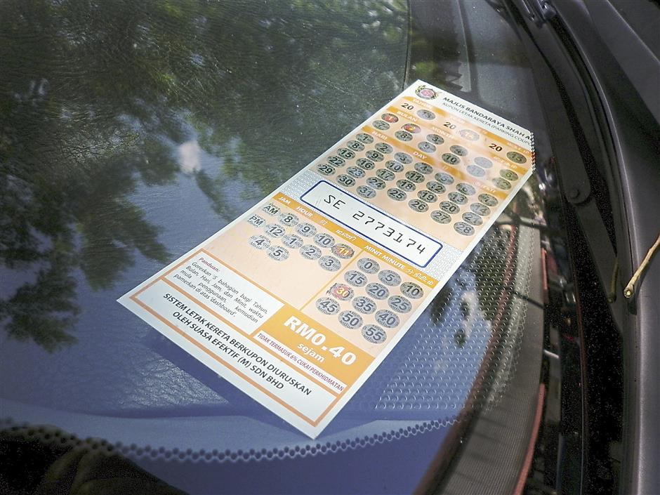 A coupon was seen displayed on a car's dashboard in Section 2, Shah Alam.