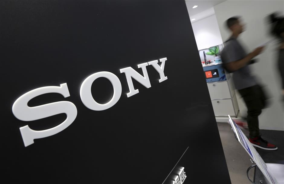 FILE - In this July 31, 2014, file photo, visitors walk past the logo of Sony Corp. at Sony Building in Tokyo. Sony Corp. said Tuesday, July 31, 2018, its profits nearly tripled in the latest quarter, boosted by a jump in PlayStation 4 software sales. (AP Photo/Eugene Hoshiko, File)