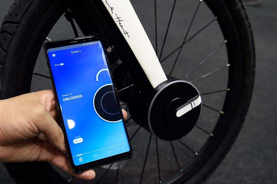 A host holds a mobilephone used to lock a Bisecu Smart Bike Lock on a bycicle at the Mobile World Congress (MWC), the world\'s biggest mobile fair, on February 26, 2018 in Barcelona. the Mobile World Congress is held in Barcelona from February 26 to March 1.  / AFP PHOTO / Josep LAGO