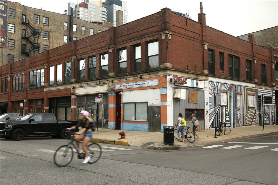 Bicyclists ride past West Randolph Street and  North Peoria Street in Chicago on Thursday, August 16, 2018. Google is planning to open a flagship retail store at this location, near West Randolph Street and North Peoria Street.   (Stacey Wescott/Chicago Tribune/TNS)