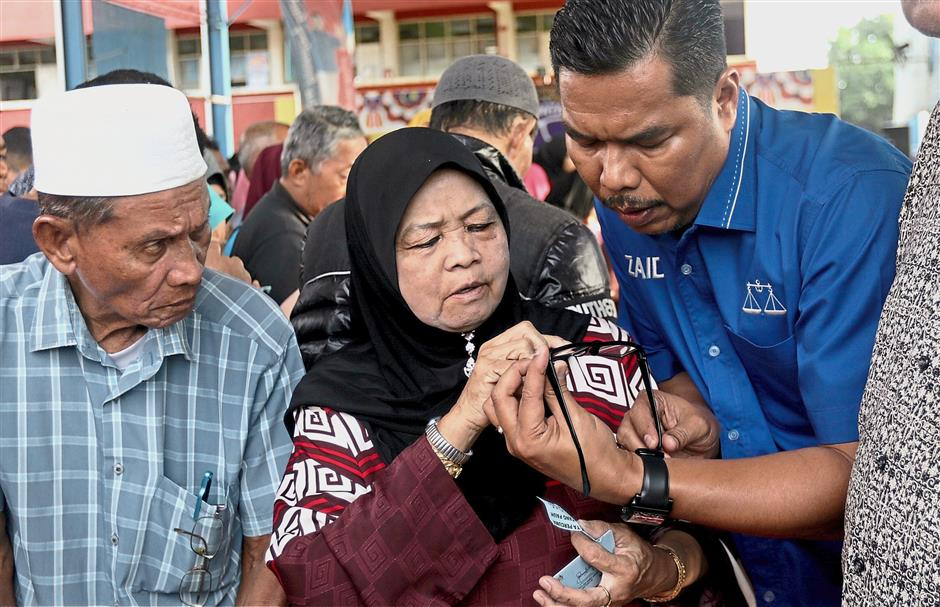 Mohd Zaidi (right) helping a woman check her free spectacles.