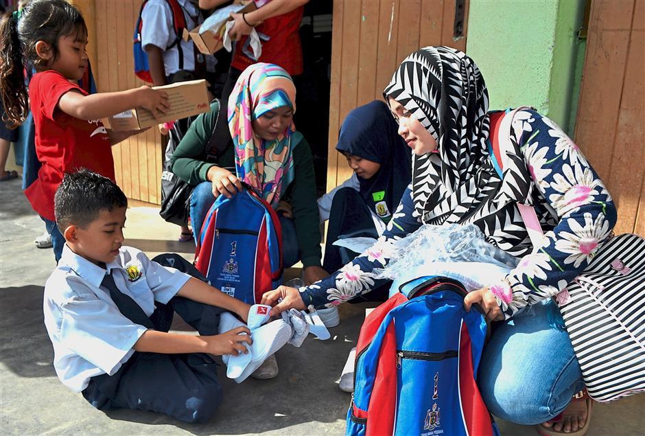 MELAKA, 1 Dis -- Aida Kadir, 29, (kanan) membantu anaknya, Muhd Luqman Mohd Helmizan,7, menyarung kasut sekolah yang diterima pada majlis Pelancaran Bantuan Sekolah Rendah Sesi Akademik 2018 hari ini.Pada majlis tersebut, seramai 327 pelajar sekolah rendah di Parlimen Tangga Batu menerima bantuan persekolahan berupa baju, kasut dan beg sekolah melibatkan peruntukan berjumlah RM65,400.Bantuan berkenaan disampaikan Ketua Menteri Melaka Datuk Seri Idris Haron.--fotoBERNAMA (2017) HAK CIPTA TERPELIHARA