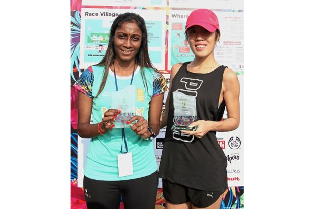 (left) Half marathon open winner S.Sanggeetha and second place Chua Khit Yeng posing with their trophies.