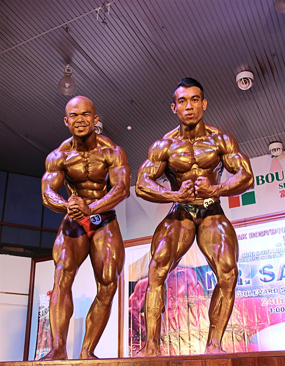 Neck to neck: Azizul (right) and Kamarrudin in action during the Light Middleweight pose-down.