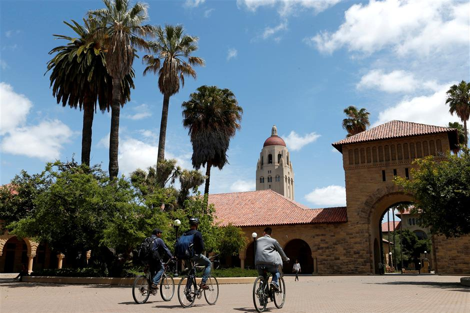 FILE PHOTO: Cyclists traverse the main quad on Stanford University\'s campus in Stanford, California, U.S. on May 9, 2014. REUTERS/Beck Diefenbach/File Photo