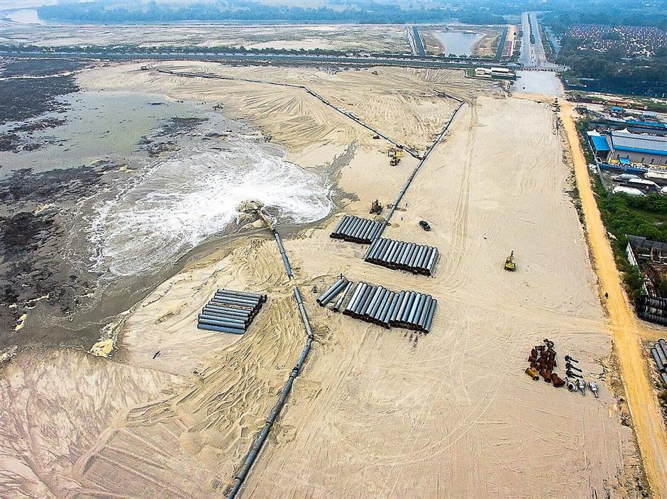 An aerial view of the suction pump pouring out sand on shore to level the area at the reclamation site in Pulau Indah.