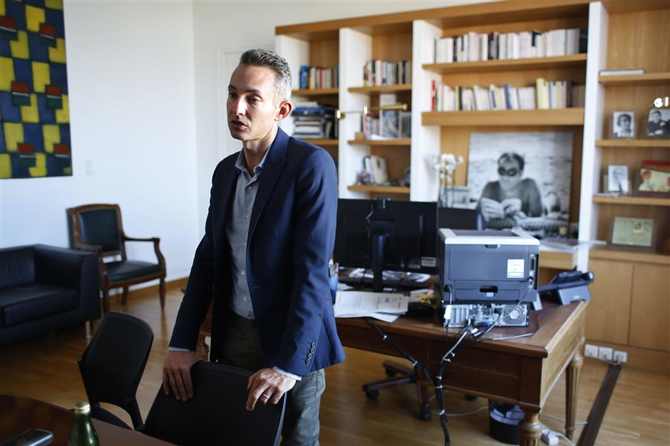 In this Tuesday, Sept. 11, 2018 photo, Paris Deputy Mayor Ian Brossat, in charge of housing, poses for a photo in his office during an interview in Paris. The spectacular growth of Airbnb in Paris, the top worldwide location for the internet giant is also raising alarms in the French capital. Some Parisians and officials at City Hall blame the site for driving Parisian families out of the city center, leading to school closures and concerns that the French capital is losing its life and charms. (AP Photo/Thibault Camus)