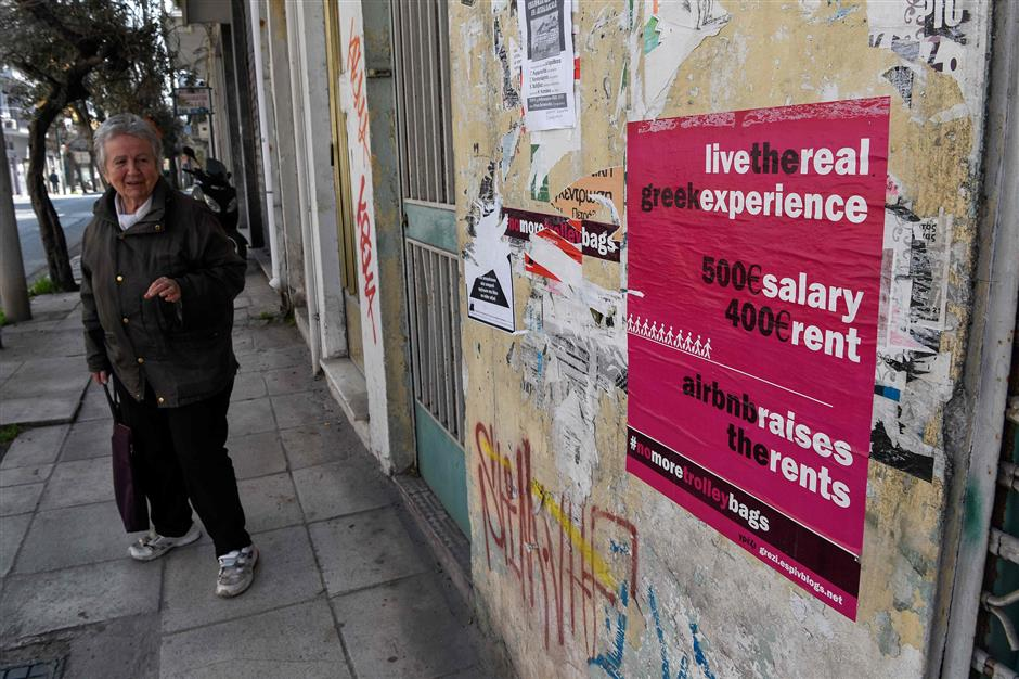 A woman walks past a poster in the Koukaki area in Athens, which in 2016 was named Airbnb\'s fifth fastest growing neighbourhood globally with an 800-percent jump in home-sharing. - The Greek chamber of hotels commissioned a Grant Thornton study that found that over 76,000 properties in Greece are available on home-sharing platforms. The study argued that declining availability had pushed up rents in central Athens by 9.3 percent in a year, disproportionately affecting poorer sections such as pensioners and single-parent families. (Photo by LOUISA GOULIAMAKI / AFP)