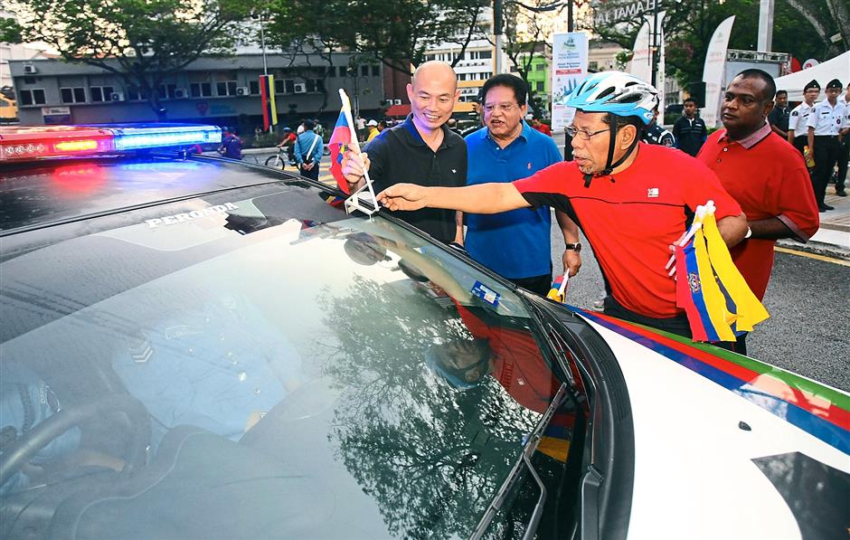 Flying the flag: Ahmad Phesal placing a Federal Territories flag on a DBKL vehicle during the 13th KL Car Free Morning yesterday. Looking on are (from left) Lim, Tengku Adnan and Dr Loga Bala.