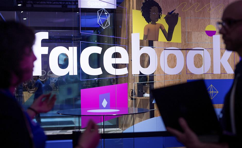 FILE - In this April 18, 2017 file photo, conference workers speak in front of a demo booth at Facebook's annual F8 developer conference, in San Jose, Calif. The U.K. for the first time on Monday April 8, 2019, proposed direct regulation of social media companies, with senior executives potentially facing fines if they fail to block damaging content such as terrorist propaganda or images of child abuse. (AP Photo/Noah Berger, File)