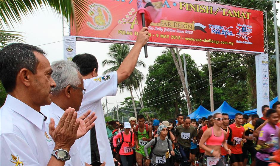 Tengku Kamarul Zaman flagging off the participants. Looking on are Mat Tahir and Tourism Ministry Pahang Office general manager Idros Yahya (left).